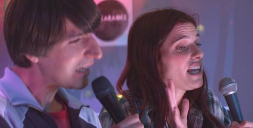 "Image of Louis and Carol singing karaoke in the film ""In a World"""