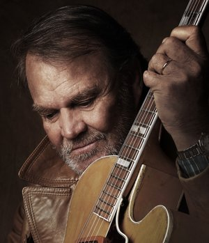 Glen Campbell stares down with a guitar raised in his hands